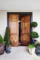 Eingangsbereich mit antiker Holztür und Buchsbäumchen