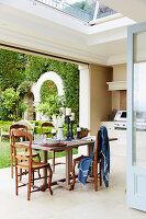 Holztisch und Stühle auf überdachter Terrasse mit Gasgrill