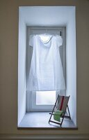 Simple white dress hung in window in place of curtain and miniature deckchair on windowsill