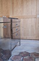 Glossy, stainless steel kitchen cabinets next to wooden door and floor in mixture of materials