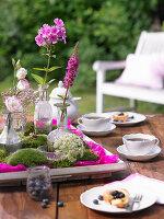 Tablett mit Moos und Blumen auf gedecktem Kaffeetisch im Garten