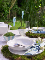 Set table decorated with moss, twigs and bird figurines