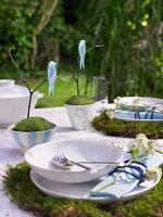 Gedeckter Tisch im Garten mit Moos, Zweigen und Vögelchen als Deko