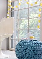Girlande aus weißen und gelben Dekoeiern um Sprossenfenster
