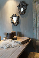 Two mirrors in ornate frames on grey wall above wooden table