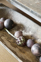 Purple Christmas-tree baubles and artichoke in wooden trough