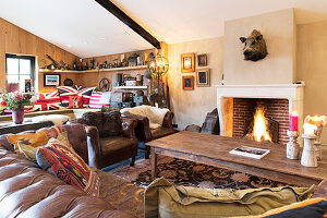 Vintage leather couch, armchair and coffee table in front of fireplace in converted barn