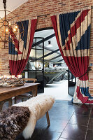 Sheepskins on bench at dining table, brick wall and Union-flag-patterned curtains screening open doorway