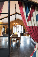 Union-flag-patterned curtains on open door with view of dining table in converted barn