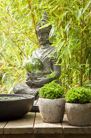 Seated Buddha statue amongst bamboo