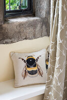 Cushion with bee motif on window seat below rustic stone window
