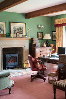 Log burner in fireplace and antique furniture in study with green walls