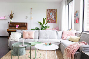 Pale grey sofa, piano and pastel accessories in living room