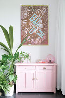 Pop art picture above pink cabinet and houseplants