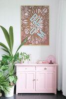 Pop-Art-Bild über rosafarbenem Schränkchen und Zimmerpflanzen