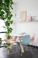 Hängende Efeutute vor dem runden Esstisch mit pastellfarbenen Stühlen