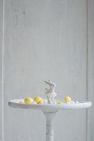 Osterhasenfigur und Marzipaneier auf weißem Tisch