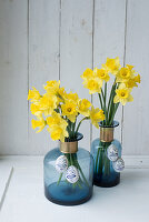 Easter eggs hung from daffodils in blue bottles