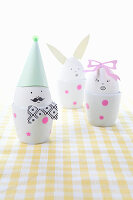 Whimsically decorated eggs in eggcups