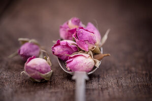 Dry rose buds on a spoon