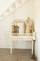 Candles in candlestick, mirror, tailors' dummy and Madonna statue on white wooden table
