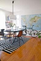Tisch mit Stühlen auf schwarz-weiß gestreiftem Teppich, im Hintergrund Farhhrad vor Landkarte im Esszimmer