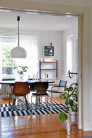 Tisch mit Stühlen auf schwarz-weiß gestreiftem Teppich vor Fenster im Esszimmer