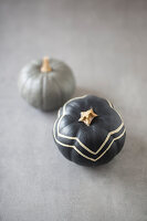 Pumpkins painted grey, one with zig-zag pattern