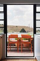 Orangefarbene Stühle am Tisch auf dem Balkon vor Wolkenhimmel