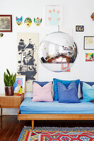 Low-hanging spherical lamp in front of couch below gallery of pictures