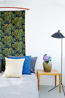 Fabric with exotic pattern of leaves used as bed headboard