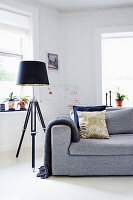 Tripod standard lamp next to grey sofa in living room