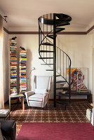 Vertical bookshelves and armchair next to spiral staircase in reading area