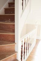 Eine alte Holztreppe mit abgenutzten Stufen und weißem Geländer