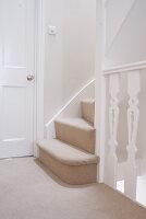 Treppe mit neu verlegtem beigem Teppich auf den Stufen