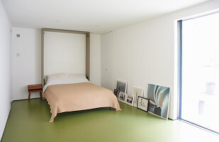 Murphy bed in minimalist room with green floor
