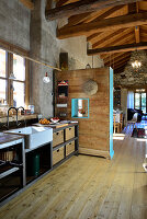 Kitchen in converted barn with concrete wall and wooden floor