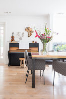 Long, colourful table and grey chairs in front of piano and stool in open-plan interior