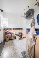 Coat hooks and wooden bench in half-height foyer with terrazzo floor