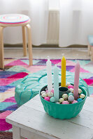 Colourful candles and baubles in turquoise bundt cake tin