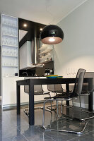 Black dining set in front of serving hatch leading to open-plan kitchen