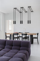 View across sofa to dining table, black chairs and pendant lamps