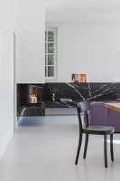 Chair in front of L-shaped, floating, black marble shelf with integrated fireplace