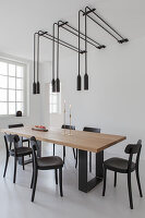 Pairs of pendant lamps above dining table in white room