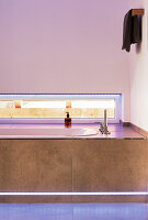 Bathtub with strip lighting below narrow horizontal window