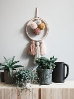 Homemade wall decorations with woollen pompoms and tassels