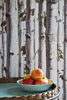 Frische Äpfel in Schüssel vor Birkentapete