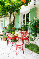 Red garden furniture in seating area outside French stone house