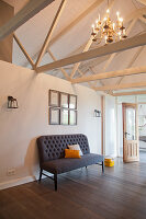 Couch against half-height partition in converted stable with exposed wooden roof structure