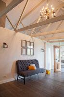 Gepolsterte Sitzbank vor halbhoher Raumteiler in umgebautem Stall mit Dachkonstruktion aus Holz